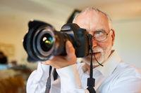 Senior als professioneller Fotograf mit Kamera