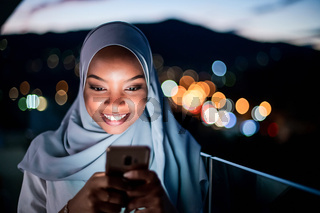 Young Muslim woman on  street at night using phone