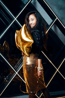 Portrait of pretty happy asian woman having fun and holding golden balloon