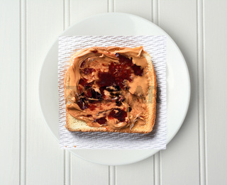 Overhead shot of a slice of toast with Peanut Butter and Jelly, on a paper napkin and white plate.