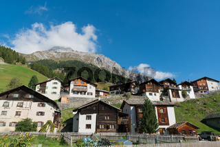 picturesque mountain village with white stone houses and stone roofs in the Swiss Alps