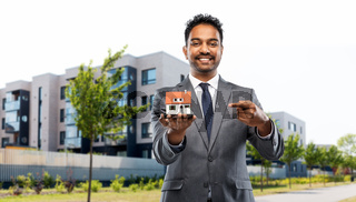 indian man realtor with house model on city street