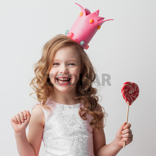 Girl in crown holding heart lollipop