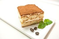 Tiramisu, traditional Italian dessert on a white plate. Close up.