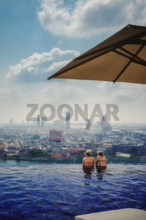 Two Girls in Bikinis Swimming in Infinity Pool Overlooking Bangkok Thailand Urban City Landscape Luxurious Vacation Destination