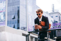 A Young And Handsome Businessman Works On The Go On His Phone