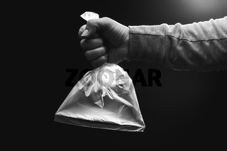 Female hand is holding a empty plastic bag filled with clean air. Environment and ecology concept.