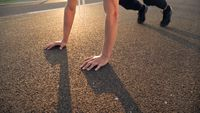 Young fit man doing push ups in the morning outdoor on road in sunset with strong sun flare