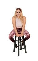 Beautiful woman sitting on a bar chair