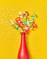 Colorful paper spirals as a champagne bubbles foam from red painted bottle.