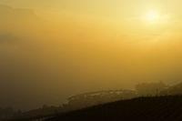 Die untergehende Sonne im goldenen Herbstnebel über dem Genfersee am Jachthafen Pichette