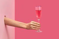 Woman's hand holds glass of rose wine with soft shadows.