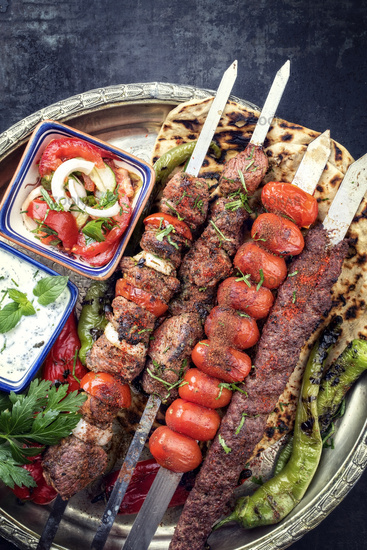 Traditional oriental Adana kebap and shashlik skewer with tomato and flatbread as top view on a plate