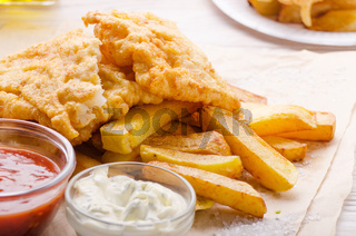 Traditional British street food fish and chips with ketchup and tartar sauces on parchment paper