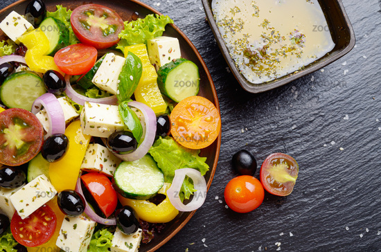 Top view at Mediterranean diet dish greek salad on slate tray with sauce aside