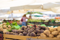 Farmers' food market stall with variety of organic vegetable. Vendor serving and chating with customers