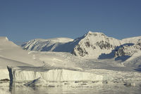 mountains and glaciers of the coast of Antarctica and icebergs in the ocean near it