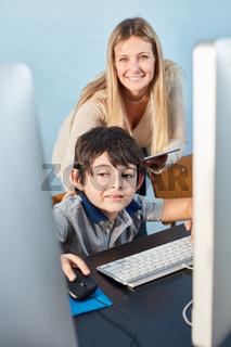 Schüler mit Lehrerin am Computer