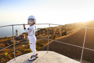 Astronaut futuristic kid girl with white full length uniform and helmet wearing silver shoes outdoors