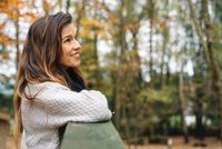 Attractive woman, relaxed in a park In autumn surrounded by colorful leaves looking to the trees pensively.