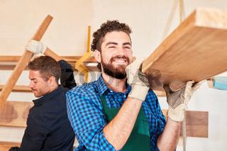 Schreiner Lehrling trägt Holz Balken