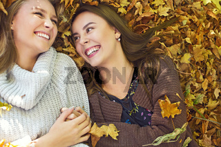 Fashionable beautiful young girlfriends together in the autumn park background. Having fun and posing.