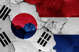 flags of South Korea and Netherlands painted on cracked wall