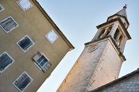 Church tower with clock on facade in Budva in Montenegro