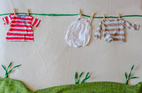 Mock scene made with babys clothes simulating a clothesline on a green meadow