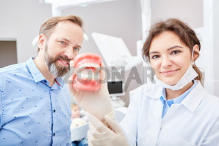 Zahnärztin mit Patient zeigt Modell von Gebiss