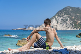 young man sitting at a stone beach and looking at the sea