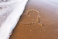 Heart drawn on the sand of the beach, soft sea wave. Love concept.