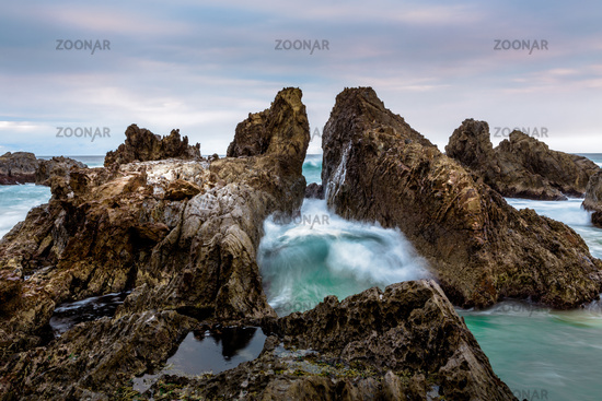 Ocean waves pushing through the dramatic jagged rock gap channel