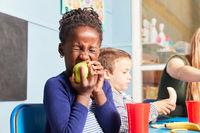 Afrikanisches Mädchen isst einen Apfel