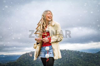 Woman holding Christmas items in snowy mountain scene