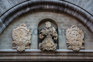 Beautiful coat of arms and statue on a historical old building