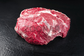 Raw dry aged wagyu beef round steak piece as closeup on black background with copy space
