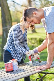 Heimwerker Paar im Garten beim lackieren der Möbel