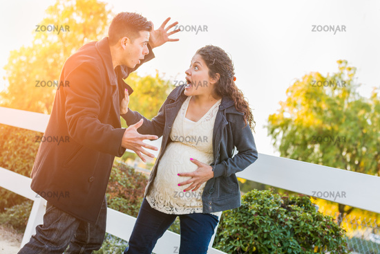 Stunned Hispanic Pregnant Young Couple In Pain Walking Outdoors