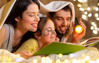 happy family reading book in bed at night at home