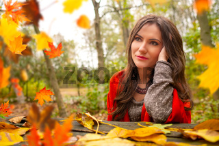 Beautiful romantic girl in park autumn scenery, sitting down at a wooden table and looking away, blurred yellow leaves are falling in the foreground. Close-up shot in natural light, vibrant colors