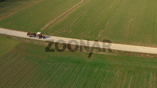 Aerial view of a red tractor and trailer carrying a load of manure on road