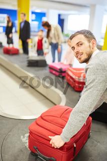 Mann als Passagier am Gepäckband holt Koffer ab