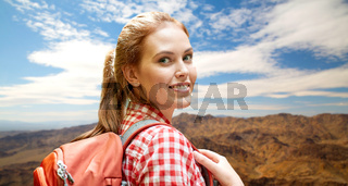 smiling woman with backpack over mountains
