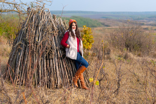 Beautiful girl smiling at the camera, in stylish fashion clothes in autumn scenery outdoors. Gorgeous romantic young woman in the countryside on a hill, in a sunny day. Full length landscape shot