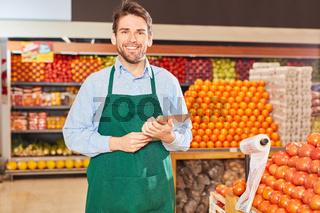 Junger Mann als Marktleiter mit Klemmbrett