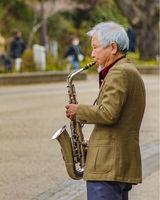 Senior Man Playing Saxophone at Park, Tokyo, Japan