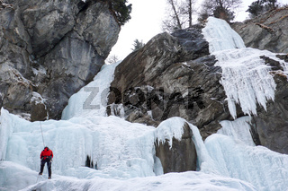 male ice climber rappelling off a steep frozen waterfall in winter