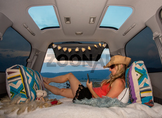 Woman relaxing in her van using mobile phone
