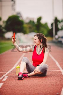 Young woman athlete at the stadium sporting lifestyle, sitting on the track, taking selfie photo on a smartphone, smiling joyful in her ears earpiece, near a bottle flask with water